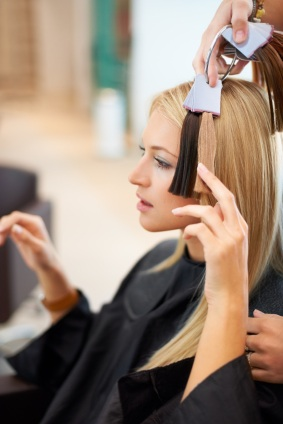 Young woman selecting the right shade of hair extensions at the salon